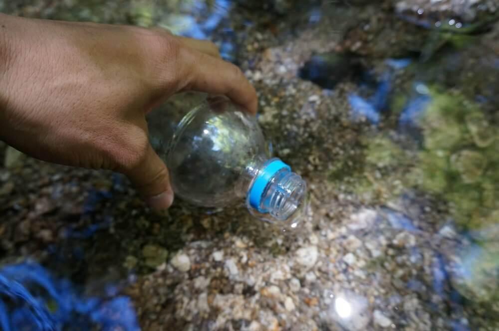ペットボトルに水をくむ人の手